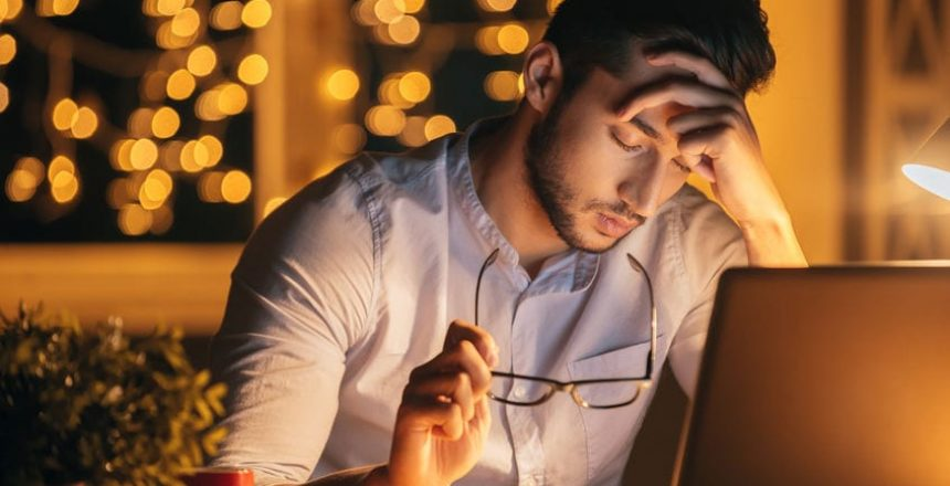 Feeling exhausted. Frustrated young man carrying eyeglasses and keeping eyes closed while sitting at his working place at night time with Christmas lights in the background